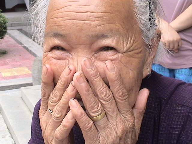 a photo of an elderly asian woman smiling with hands to her face