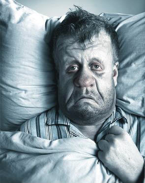 photo of a man sick in bed suffering with a stuffy, red nose