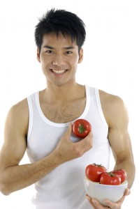 sexy asian man holding a bowl of tomatos