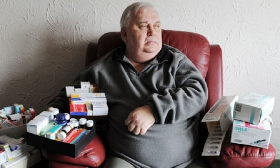 image of a very overweight man sitting in a chair surrounded by boxes of medications.